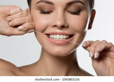 Close up of female face with perfect smile. Girl is cleaning teeth by special thread. Isolated
