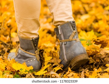 Close up of female feet walking on the autumn ground.