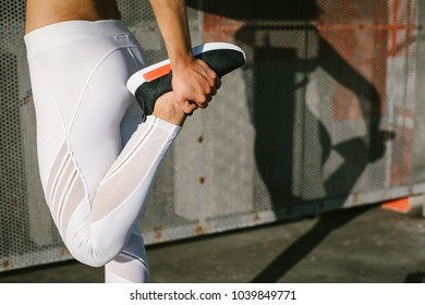 Close up of female fit athlete stretching legs during running and fitness urban workout.