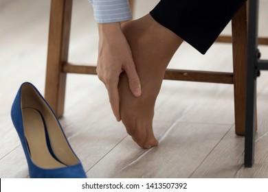 Women wearing high heels brown shoes, massaging tired legs
