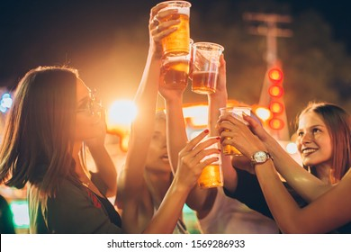 Close up of female friends cheering with beer in amusement park