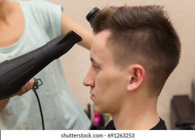 close up of female hairdresser drying her male customer's hair in her hairdressing salon.
