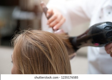 Close up of female hairdresser in a white coat with a brown hairdryer and hairbrush blow-drying red hair of visitor or model of the beauty salon.