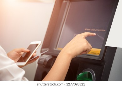 Close up of female hand entering on screen at an ATM. Finger about to press and holding smartphone in other hand. Automated teller machine
