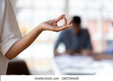 Close up female hand folded fingers in mudra gesture. Businesswoman take beak during busy stressful workday, do yoga exercise meditating at workplace, no stress, reduce fatigue anxiety at work concept