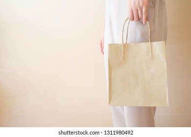 Close up of female hand holding blank brown paper bag with handle over white background. Copy space for your text or design logo. Mock-up of shopping bag packaging.