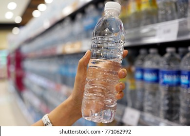 Close up female hand holding a bottle of water or mineral water in grocery store.