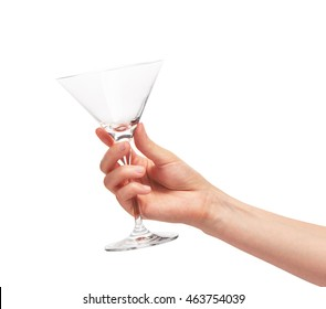 Close up of female hand holding empty clean transparent martini glass against white background. Clipping path for glass border included.