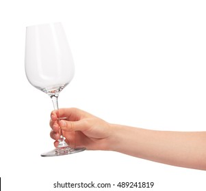 Close up of female hand holding empty clean transparent wine glass against white background. Clipping path for glass border included.