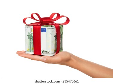 Close up of female hand holding gift box made of euro banknotes isolated on white background