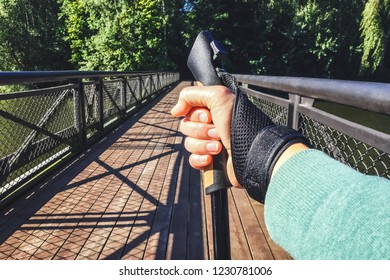 Close up of female hand holding Nordic walking pole on bridge. Concept of healthy lifestyle. Point of view shot