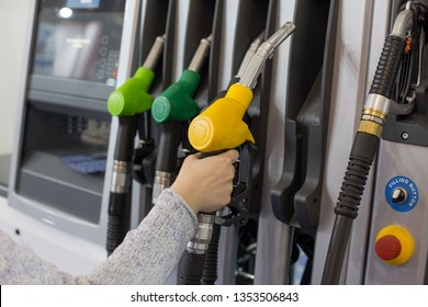 Close up of female hand holding nozzle for petrol for filling station