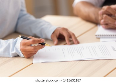 Close up female hand holding pen ready to put signature on official paper, document, contract. Job candidate intern making deal for paid traineeship, reading, filling and singing agreement