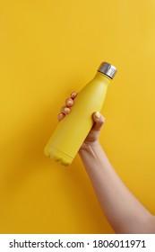 Nahaufnahme der weiblichen Hand, mit gelber wiederverwendbarer Stahlflasche auf gelbem Hintergrund