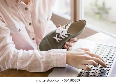 A close up of a female hand with a keyboard and shoes, buying things on the internet