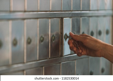 Close up of a female hand opening a mailbox with a small key - post office box or PO BOX concept - bank deposit box