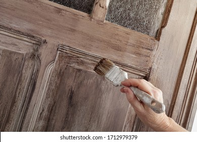 close up female hand painting an old door inside a house with a brown patina