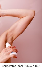 Close up of female hand preventing skin from perspiring. Girl is standing and holding antiperspirant in hand while rolling it on body.