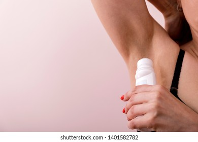 Close up of female hand preventing skin from perspiring. Girl is standing and holding antiperspirant in hand while rolling it on body