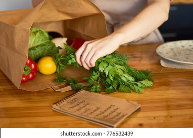 Close up of female hand taking fresh vegetables out of paper bag with groceries on kitchen counter, preparing to cook delicious dinner