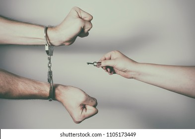 Close up of a female hand, unlocking male from handcuffs by key and send him free. Divorce concept.