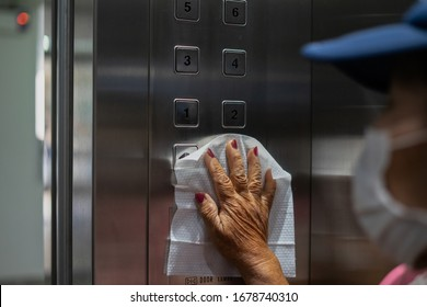 Close up of female hand using wet wipe to clean an elevator push button control panel before touc.Antiseptic,disinfection ,cleanliness and heathcare, anti virus concept. anti Corona virus (COVID-19).