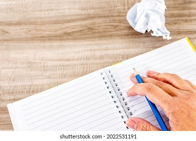 Close up of female hand writing in a notebook, on a wooden desk.