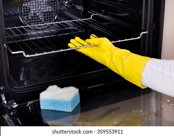 Close up of female hand with yellow protective gloves cleaning oven