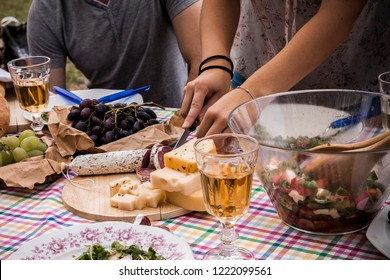 close up of female hands cutting salami and cheese on a picnic table woth wine and salad