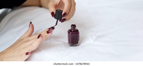 Close up female hands doing nail polish in red color on white linen bed, fashion and beauty concept, banner style for text