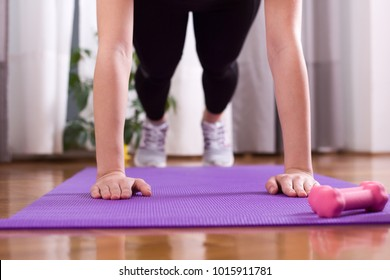 Close up of female hands doing pushups on yoga mat on floor at home