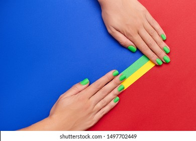 Close up of female hands with green nails on a multicolored background