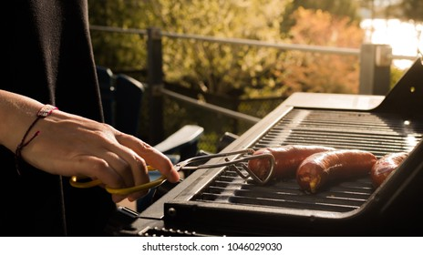 Close up of female hands grilling sausage on propane barbecue on warm summer day
