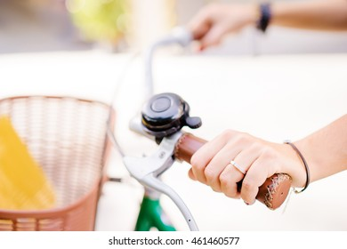 Close up of female hands holding bicycle handlebar.