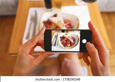 Close up of female hands holding cellphone and photographing fresh salad in cafe