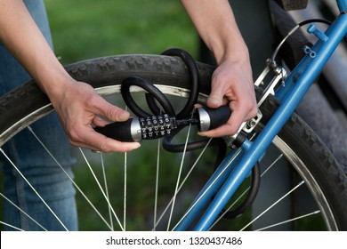Close up of female hands holding combination bike lock in front of bicycle