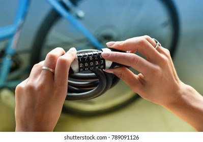 Close up of female hands holding combination bike lock with bicycle blurred in background