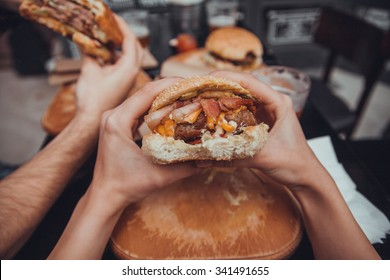Close Up Of Female Hands Holding Delicious Bacon Burger