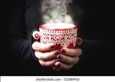 Close up of female hands holding red mug with hot drink on black background