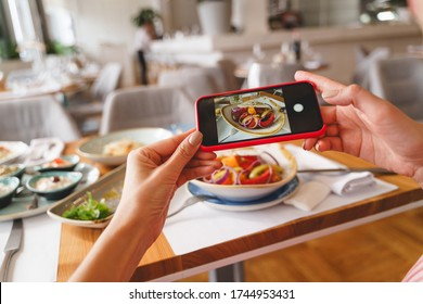 Close up of female hands holding smartphone and photographing fresh salad in cafe
