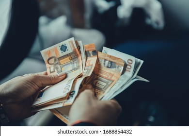 Close up of female hands holding a stack of 50 and 100 euro banknotes and counting them