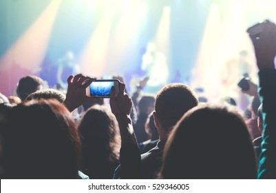 Close up female hands holding their smartphone and photographing rock concert