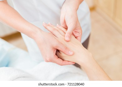 Close to the female hands of the masseur make a point massage of the hands in the cosmetology room