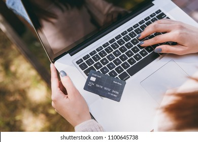 Close up female hands on keyboard. Woman sitting on bench holding credit card, working on modern laptop pc computer in city park in street outdoors. Mobile Office. Online shopping, business concept