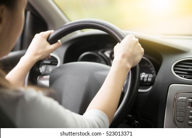 Close up of female hands on the steering. Traveler girl on car trip, looking at the road. View over shoulder