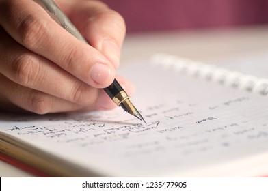 Nahaufnahme von weiblichen Händen mit Stift, der auf Notebook-Notebook aufschreibt