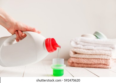 Close up of female hands pouring liquid laundry detergent into cap on white rustic table with towels on background in bathroom.