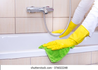 Close up of female hands with rubber gloves cleaning bathtub