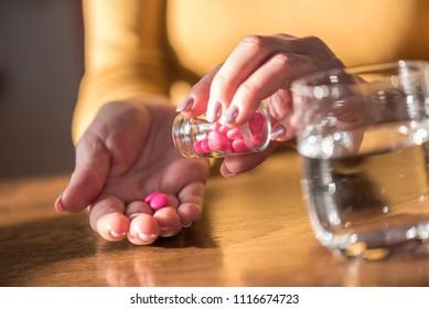 Close up of female hands taking medication, hard light