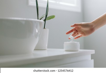 Close up of female hands taking moisturizing cream from bottle in bathroom. Woman taking care of her dry complexion.